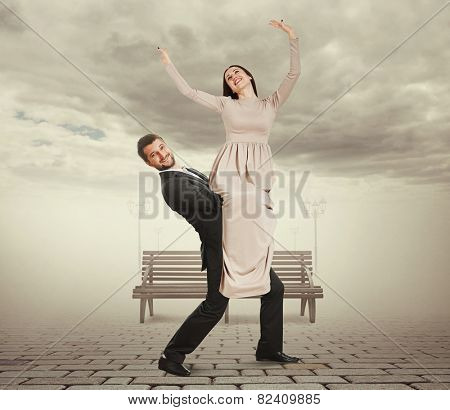 handsome young man holding his woman with pleasure and going forward at outdoor