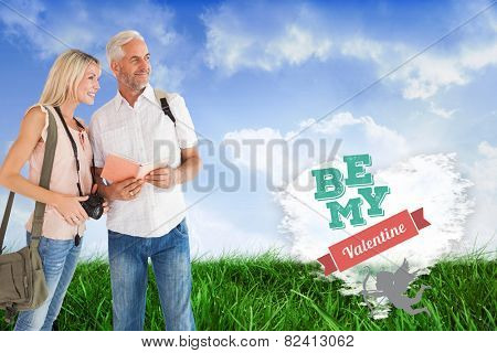 Happy tourist couple using the guidebook against cloud heart