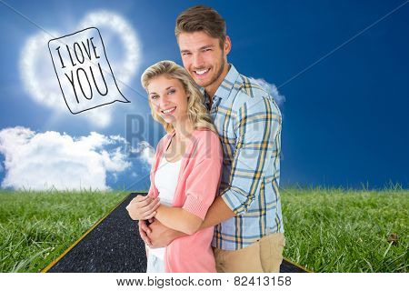 Attractive couple embracing and smiling at camera against road on grass