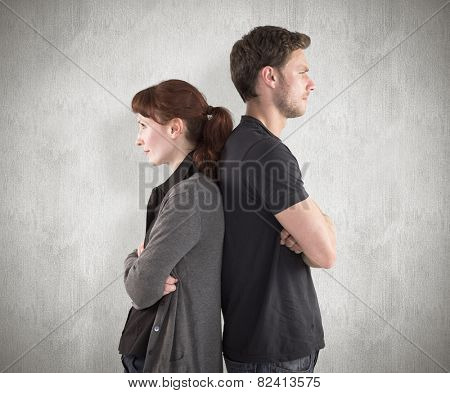 Irritated couple ignoring each other against weathered surface