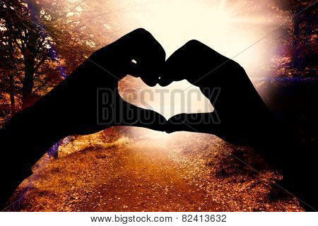 Woman making heart shape with hands against forest trail
