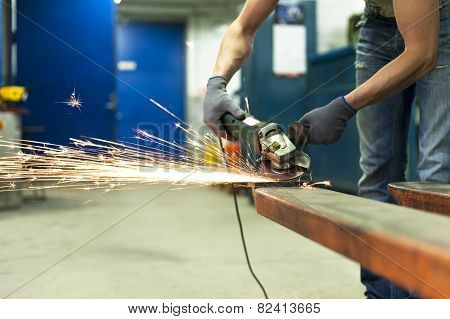 Man Hands Sawing Metal With Sparks In Workshop. Metalworking.