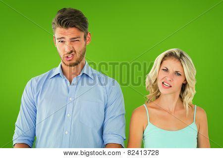 Young couple making silly faces against green vignette