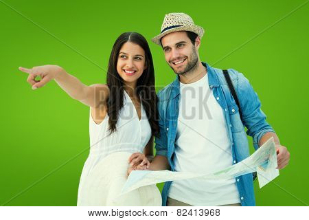 Happy hipster couple looking at map against green vignette