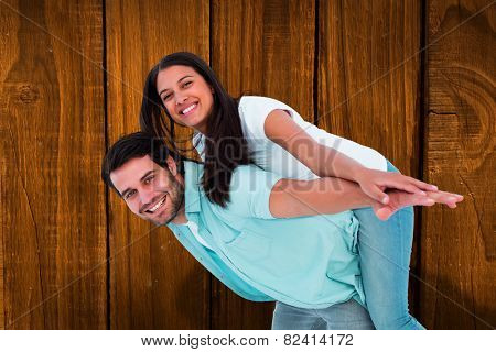Happy casual man giving pretty girlfriend piggy back against overhead of wooden planks
