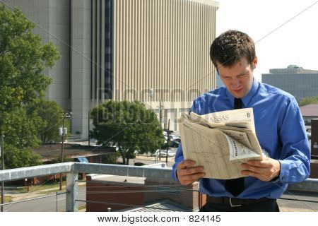 Man and Newspaper in City
