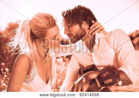 Handsome man serenading his girlfriend with guitar in sepia tones