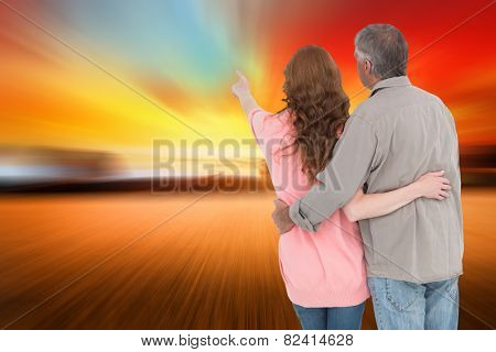 Casual couple standing arms around against countryside scene
