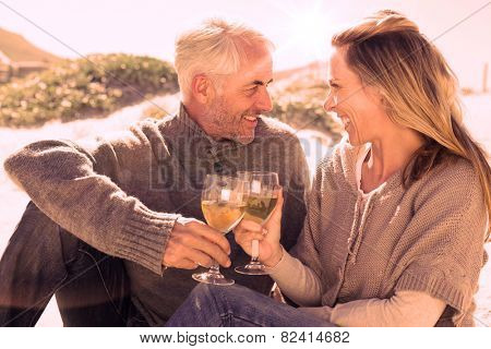 Couple enjoying white wine on picnic at the beach on a bright but cool day