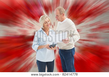 Mature couple working out their bills against love heart pattern