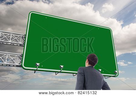 Businessman standing with hand on hip against sky