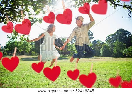 Cute couple jumping in the park together holding hands against hearts hanging on a line