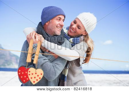 Attractive couple hugging on the beach in warm clothing against hearts hanging on the line