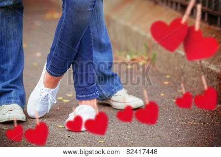 Hip young couple standing by railings against hearts hanging on a line