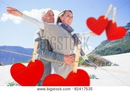 Carefree couple hugging on the beach in warm clothing against hearts hanging on a line