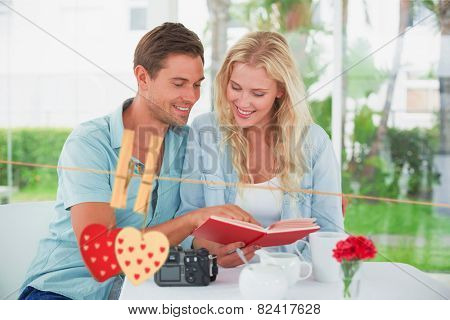 Cute hipster couple reading book together at table against hearts hanging on the line