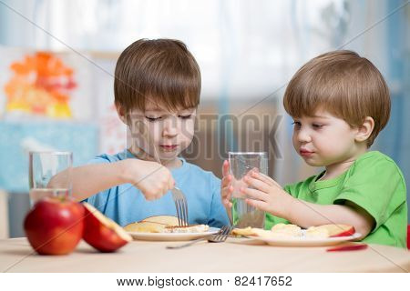 children boys eating healthy food at home