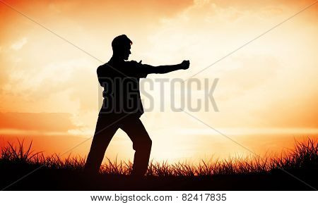 Handsome man in white doing tai chi against orange sunrise
