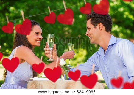 Couple with champagne flutes sitting at outdoor caf�?�© against hearts hanging on a line