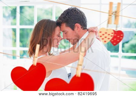 Loving young couple with arms around against hearts hanging on the line