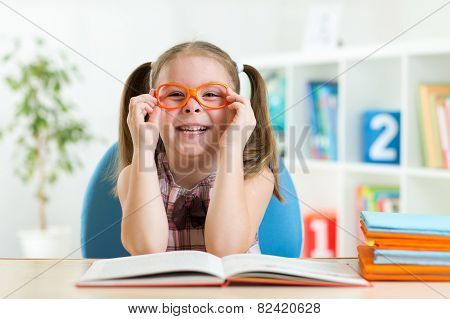 Cute little girl reading a book while wearing glasses