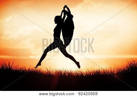 Gorgeous fit blonde leaping with scarf against orange sunrise