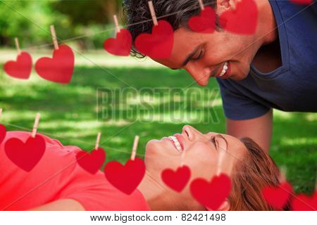 Man smiling as he looks down into his friends eyes against hearts hanging on a line