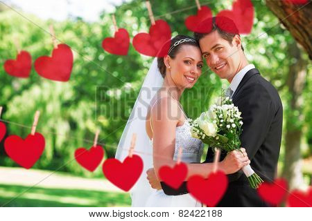 Hearts hanging on a line against loving newly wed couple in garden