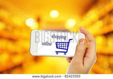 Mobile shopping concept. Hand holding mobile phone for internet shopping on supermarket background