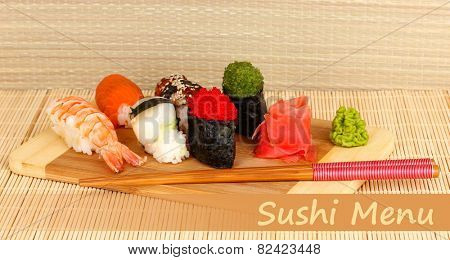 Delicious sushi served on wooden board on bamboo mat with space for your text
