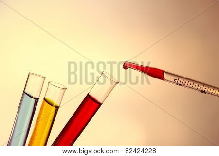 Pipette adding fluid to the one of test-tubes on light background