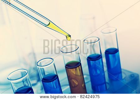 Pipette adding fluid to the one of test-tubes close-up
