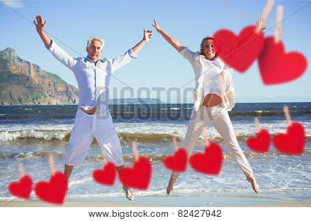 Happy couple jumping on the beach together against hearts hanging on a line