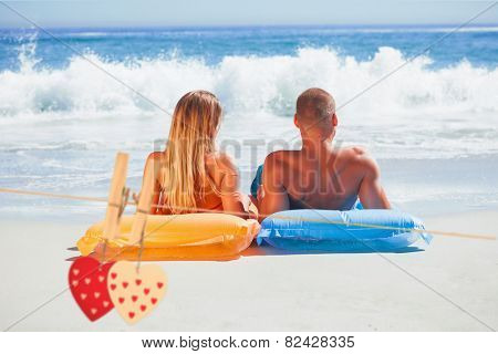Cute couple in swimsuit sunbathing together against hearts hanging on the line
