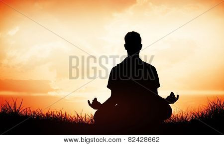 Handsome man in white meditating in lotus pose against orange sunrise