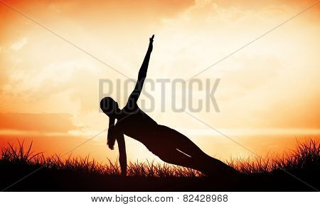 Fit woman doing pilate exercises in the fitness studio against orange sunrise