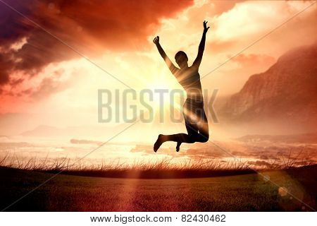 Sporty blonde jumping with arms out against sunrise over magical sea