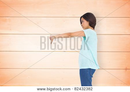 Disappointed brunette giving thumbs down against wooden planks