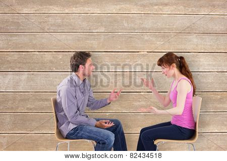 Sitting couple having an argument against wooden surface with planks