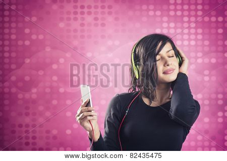 Young happy girl listening to music with headphones and mp3 player with eyes closed, in calm and relaxed mood, isolated on pink disco background.
