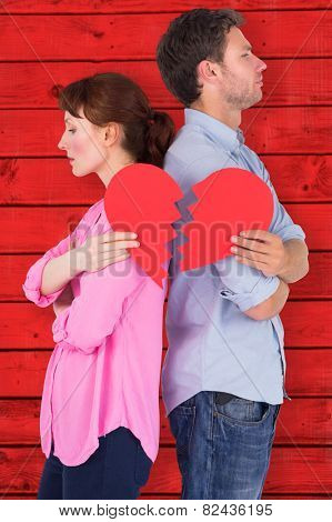 Couple holding a broken heart against red wooden planks