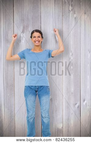 Happy brunette cheering against wooden planks background