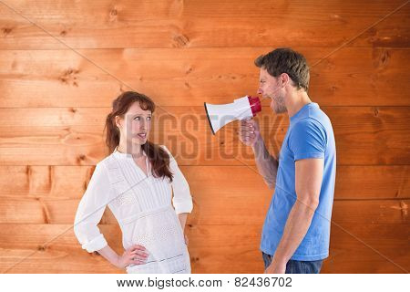 Man shouting through a megaphone against overhead of wooden planks