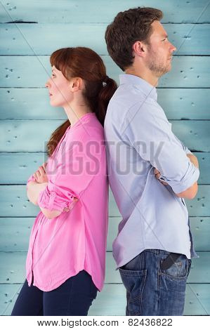 Irritated couple ignoring each other against wooden planks