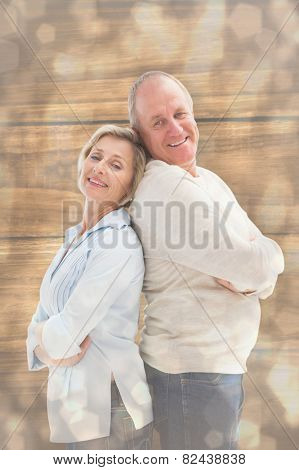Mature couple standing and smiling at camera against light glowing dots design pattern