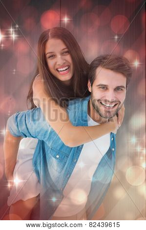 Happy hipster giving his girlfriend a piggy back against light design shimmering on red