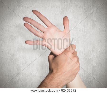 Womans wrist held by man against weathered surface