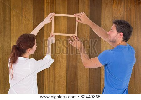 Couple deciding to hang picture against wooden surface with planks
