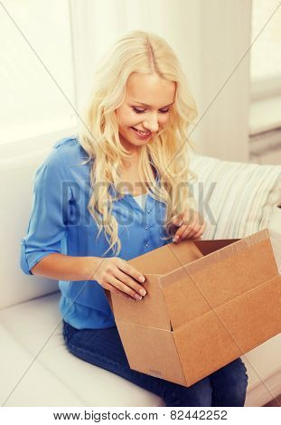home, post, delivery and happiness concept - smiling young woman opening cardboard box at home