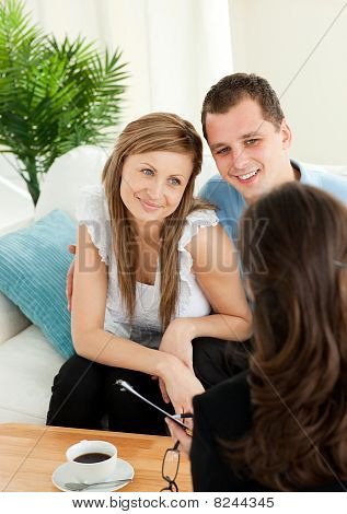 Affectionate Couple Listen To A Saleswoman Siting On A Sofa